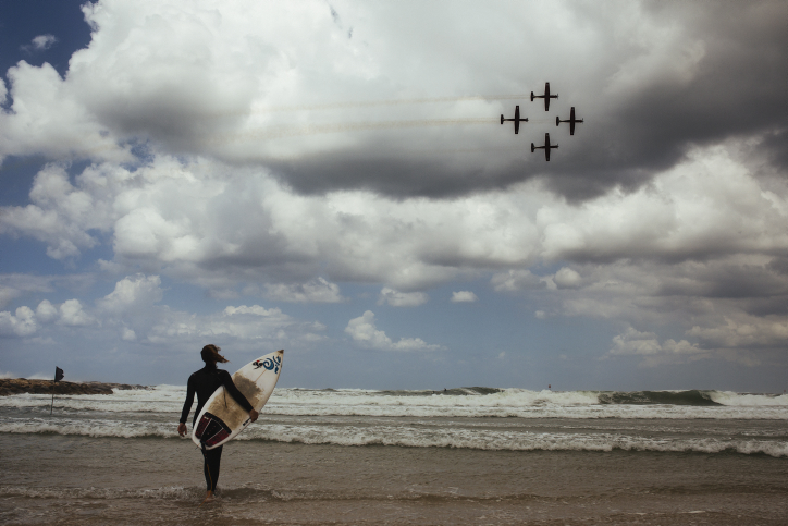 A surfer watches and Israeli Air Force aerial acrobatics demonstration on the 67th Independence Day of Israel over the beach in Tel Aviv on April 23, 2015. (Photo credit: Matanya Tausig/Flash90)