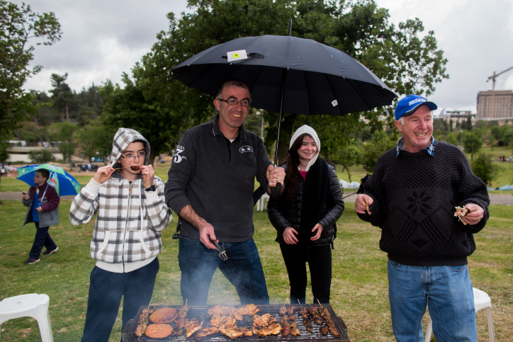 A group of Israelis enjoy a barbecue in the park despite the inclement weather to celebrate the 67th Independence Day of Israel in Jerusalem on April 23, 2015. (Photo credit: Yonatan Sindel/Flash90)