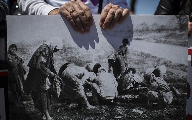 An Armenian demonstrator holds up a historic photograph of the Armenian genocide during a demonstration in Jerusalem, April 24, 2015 photo credit: Hadas Parush/Flash90