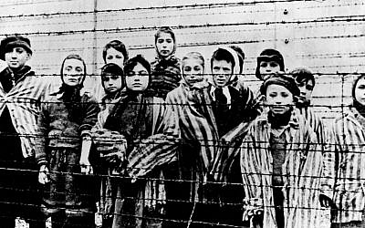 A picture taken just after the liberation by the Soviet army in January 1945 shows a group of children wearing concentration camp uniforms behind barbed wire fencing in the Auschwitz Nazi concentration camp. (AP Photo/File)