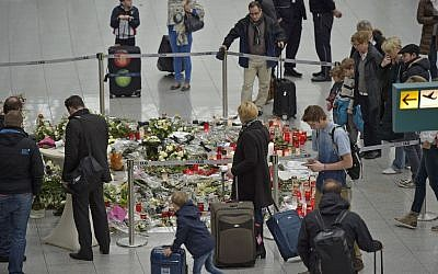 Passengers watch candles and flowers for the victims of the plane crash at the airport in Dusseldorf , Germany, Tuesday, March 31, 2015. (photo credit: AP/Martin Meissner)