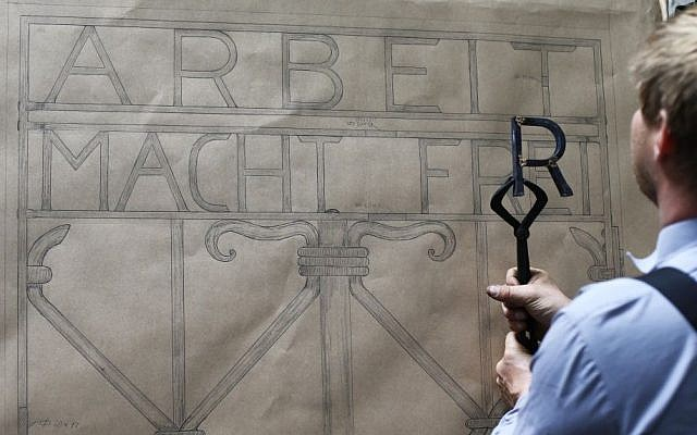 """Construction plans hang in a workshop of blacksmith Michael Poitner as he works on a replica of the Dachau Nazi concentration camp gate with the writing """"Arbeit macht frei"""" (Work Sets you Free) in Biberbach near Dachau, Germany, Thursday, April 16, 2015. (Photo credit: AP/Matthias Schrader)"""