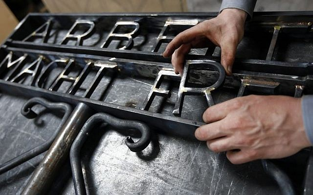 """Blacksmith Michael Poitner works on a replica of the Dachau Nazi concentration camp gate with the writing """"Arbeit macht frei"""" (Work Sets you Free) in Biberbach near Dachau, Germany, Thursday, April 16, 2015. (Photo credit: AP/Matthias Schrader)"""
