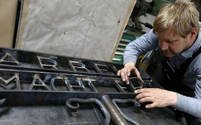"""Blacksmith Michael Poitner works on a replica of the Dachau Nazi concentration camp gate with the writing """"Arbeit macht frei"""" (Work Sets you Free) in Biberbach near Dachau, Germany, Thursday, April 16, 2015. The original gate was stolen in November 2014. (Photo credit: AP/Matthias Schrader)"""