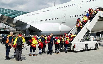 Members of a German rescue organization board a plane at the airport in Frankfurt, central Germany, Sunday, April 26, 2015, for their flight to earthquake-torn Nepal. (Christoph Schmidt/dpa via AP)