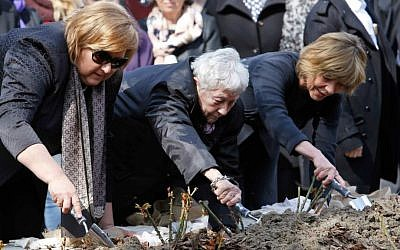 Poland's First Lady Anna Komorowska (left); Annette Chalut, camp survivor (center); and Germany's First Lady Daniela Schadt (right), plant roses at the former Nazi concentration camp of Ravensbrueck in Fuerstenberg, northeastern Germany, on April 19, 2015, to commemorate the 70th anniversary of the liberation of the camp by the Red Army on April 30, 1945. (photo credit: AP/Ferdinand Ostrop)