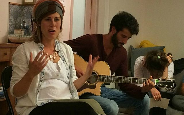 Sasha Leshem (left) leads singing and Jonah Clarfield play guitar at 'Zikaron Basalon' gathering in Jerusalem, April 15, 2015. (photo credit: Renee Ghert-Zand/Times of Israel staff)