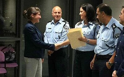 Recent immigrant Harriet Shakked receives her Civil Guard graduation certificate from course commander Police Officer Mirit Hadar, Tel Aviv, April 16, 2015. (photo credit: Renee Ghert-Zand/Times of Israel staff)