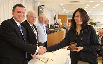 Lucy Aharish, journalist, news anchor and actress, receives a medal from Knesset Speaker Yuli Edelstein on Monday, April 20, 2015. (Photo credit: Knesset)