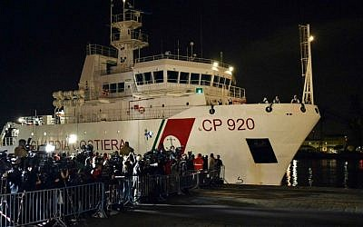 Italian Coast Guard ship Bruno Gregoretti, carrying survivors of the boat that overturned off the coasts of Libya Saturday, arrives at Catania Harbor, Italy, Monday, April 20, 2015. (AP Photo/Carmelo Imbesi)