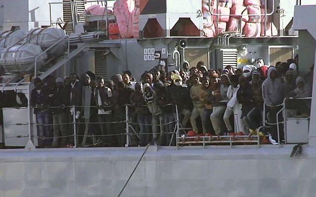 Migrants crowd at the rail aboard an Italian navy vessel as it cruises towards Italian port of Messina, Saturday April 18, 2015. (photo credit: AP/APTV)