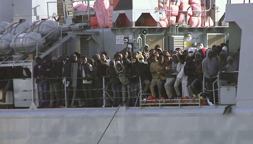 Migrants crowd at the rail aboard an Italian navy vessel as it cruises towards Italian port of Messina, Saturday April 18, 2015. (photo credit: AP/APTV)
