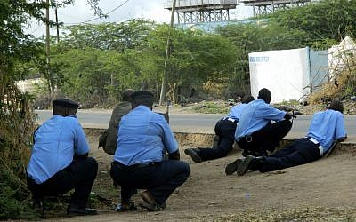 Kenyan police officers take cover outside the Garissa University College during an attack by gunmen in Garissa, Kenya, Thursday, April 2, 2015.  (photo credit: AP)