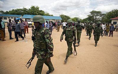 Kenya Defense Forces (KDF) soldiers arrive at a hospital to escort the bodies of the attackers to be put on public view, in Garissa, Kenya Saturday, April 4, 2015. Authorities displayed the bodies of the alleged attackers involved in the killings at Garissa University College on the bed of a pickup truck that drove slowly past the crowd gathered in a large open area. (photo credit: AP/Ben Curtis)
