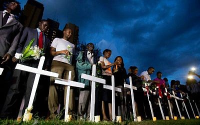 Kenyans light candles next to a white wooden cross for each of the victims of the Garissa attack, during a vigil at Uhuru Park in Nairobi, Kenya, Tuesday, April 7, 2015. (AP Photo/Ben Curtis)
