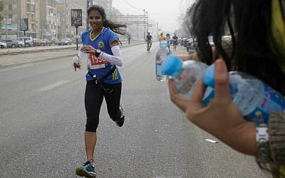 An Egyptian volunteer holds water bottles for passing runners participating in Cairo's annual Half Marathon in the Heliopolis district in Cairo, Egypt, Friday, April 17, 2015. (AP Photo/Amr Nabil)