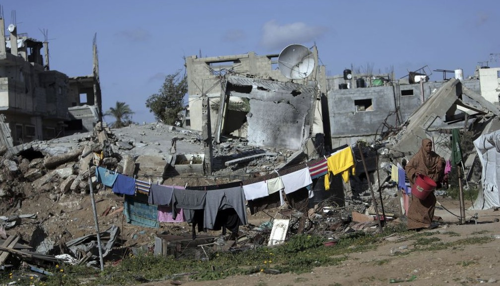 A Palestinian woman hangs washing next to the rubble of her destroyed house, in the Shijaiyah neighborhood of Gaza City, Monday, March 30, 2015. (AP/Khalil Hamra)