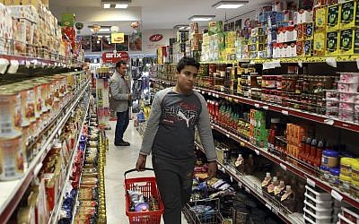 Iranians shop in a supermarket in north Tehran, Iran, April 29, 2015. Iran has removed the country's wealthiest citizens off a list of people receiving monthly handouts in a small step toward easing the burden on the budget and freeing up more government funds. (Photo credit: Vahid Salemi/AP)