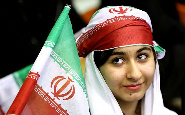 In this June 2, 2014 photo, an Iranian woman holds an Iranian flag during a ceremony in Tehran for the national soccer team. (AP/Ebrahim Noroozi)