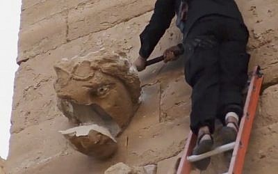 A piece falls off from a curved face on the wall of an ancient building as a militant hammers it in Hatra, Iraq, a large fortified city recognized as a UNESCO World Heritage site, April 3, 2015 (Photo credit: AP Photo/Militant video)