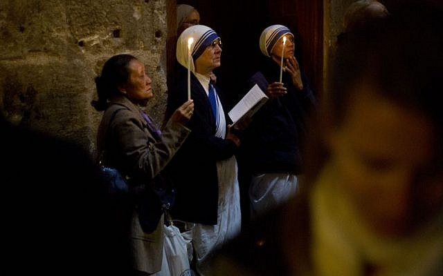 Christian women and nuns pray in the Church of the Holy Sepulcher, traditionally believed by many to be the site of the crucifixion and burial of Jesus Christ, during Orthodox Palm Sunday, in Jerusalem, Sunday, April 5, 2015. (photo credit: AP/Ariel Schalit)