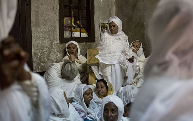 Ethiopian Orthodox Christian women pray at Deir El Sultan outside the Church of the Holy Sepulcher, traditionally believed by many to be the site of the crucifixion and burial of Jesus Christ during Orthodox Palm Sunday, in Jerusalem, Sunday, April 5, 2015. (photo credit: AP/Ariel Schalit)