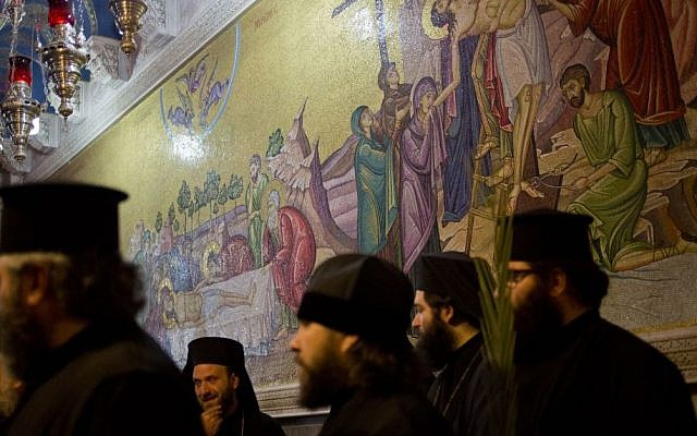 Greek Orthodox priests hold palm fond in the Church of the Holy Sepulcher, traditionally believed by many to be the site of the crucifixion and burial of Jesus Christ during Orthodox Palm Sunday, in Jerusalem, Sunday, April 5, 2015. (photo credit: AP/Ariel Schalit)