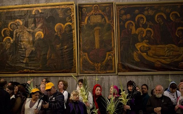 Greek Orthodox worshipers hold a palm frond in the Church of the Holy Sepulcher, traditionally believed by Christians to be the site of the crucifixion and burial of Jesus, during Orthodox Palm Sunday, in Jerusalem, Sunday, April 5, 2015. (AP/Ariel Schalit)