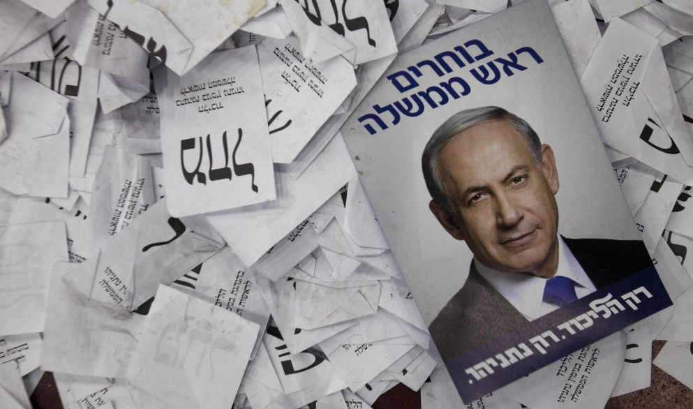 This Wednesday, March 18, 2015 photo, shows Israeli Prime Minister Benjamin Netanyahu election campaign poster lying among ballot papers at his party's election headquarters in Tel Aviv. (Photo credit: AP/Dan Balilty)