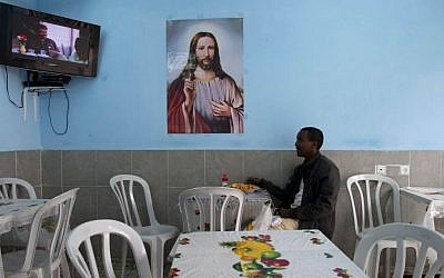 An African migrant sits at a restaurant in Tel Aviv, Israel, Tuesday, April 21, 2015. (Photo credit: AP/Oded Balilty)