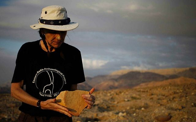 In this photo taken Thursday, March 19, 2015, archaeologist Morag Kersel holds a pottery shard found at a Bronze Age cemetery, known as Fifa, in southern Jordan. (AP Photo/Sam McNeil)