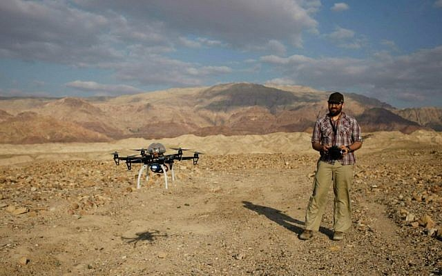 In this photo taken Thursday, March 19, 2015, Chad Hill, an archaeologist at the University of Connecticut, operates a drone to survey looting at a 5,000-year-old cemetery known as Fifa in southern Jordan. (AP Photo/Sam McNeil)