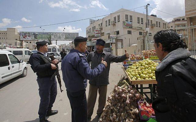Palestinian policemen talk to a merchant in the West Bank town of Azariya, April 13, 2015. (photo credit: AP/Nasser Shiyoukhi)
