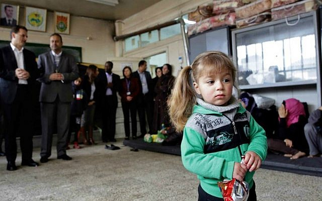 A girl holds a snack at a school, during the visit of Pierre Krahenbuhl, commissioner-general of the United Nations Relief and Works Agency (UNRWA), background left, in Yarmouk refugee camp in Damascus, Syria, Sunday, April 12, 2015. (AP Photo)