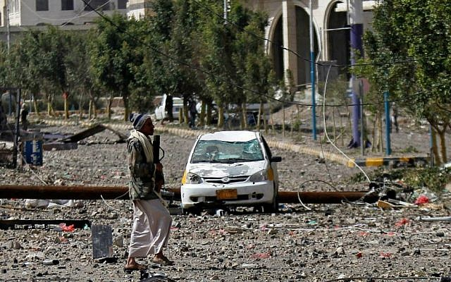A Shiite fighter known as a Houthi walks on a street littered by debris after a Saudi-led airstrike hit a site where many believe the largest weapons cache in Yemen's capital, Sanaa, is located on Monday, April 20, 2015. (AP Photo/Hani Mohammed)