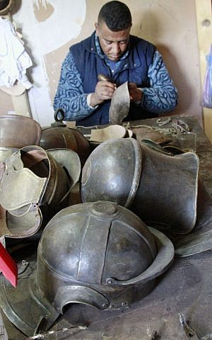 A Moroccan member of the costumes department puts the finishing touches on Roman helmet for the TV series A.D. in the city of Ouarzazate, Morocco.  (photo credit: AP Photo/ Paul Schemm)