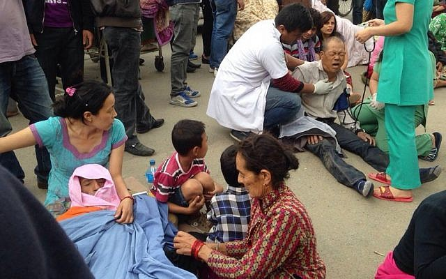 An injured man receives treatment outside the Medicare Hospital in Kathmandu, Nepal, Saturday, April 25, 2015. (Photo credit: AP/ Niranjan Shrestha)