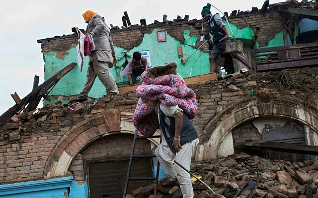 Residents rescue items from debris of a house that was damaged in Saturday's earthquake in Kathmandu, Nepal, Monday, April 27, 2015. (AP Photo/Bernat Armangue)