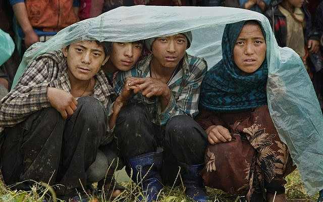 Villagers wait in the rain as an aid relief helicopter lands at their remote mountain village of Gumda, near the epicenter of Saturday's massive earthquake in the Gorkha District of Nepal, Wednesday, April 29, 2015. (photo credit: AP Photo/Wally Santana)