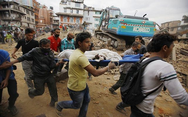 Volunteers carry the body of a victim on a stretcher, recovered from the debris of a building that collapsed after an earthquake in Kathmandu, Nepal, Saturday, April 25, 2015. (photo credit: AP Photo/ Niranjan Shrestha)