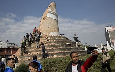 A man takes a selfie at the historic Dharahara Tower, a city landmark, that was damaged in Saturday's earthquake in Kathmandu, Nepal, Monday, April 27, 2015. (photo credit: AP/Bernat Armangue)