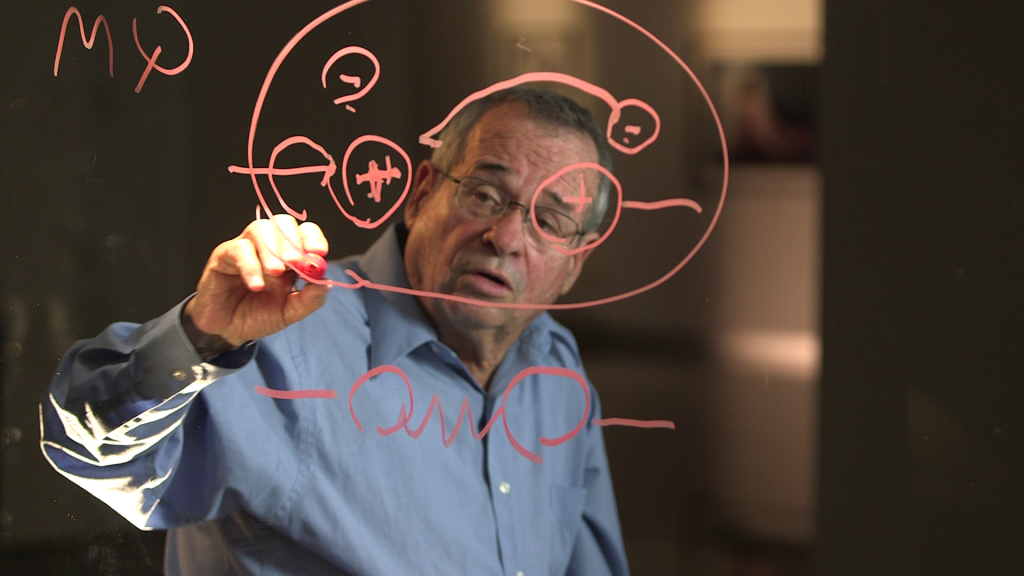 Nobel Laureate Arieh Warshel describing his theory on the see-thru board that Uri Rosenwaks used throughout the five-chapter series (Courtesy Ruth Diskin Films)