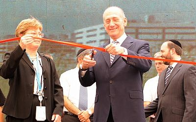 Former prime minister Ehud Olmert, with Intel Israel General Manager Maxine Fassberg, cuts the ribbon at the opening of Intel's new R&D center in Jerusalem, 2009 (Courtesy Intel)