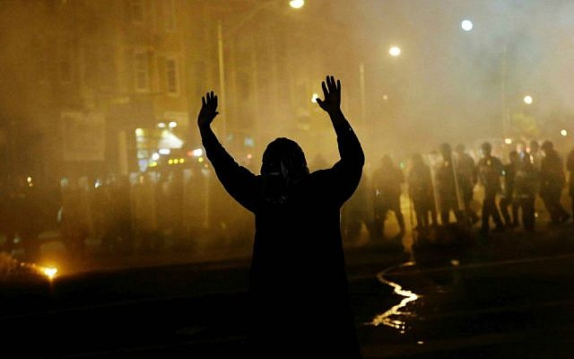 A protester walks away as police in riot gear advance on the crowd after a 10 p.m. curfew went into effect in the wake of Monday's riots following the funeral for Freddie Gray, Tuesday, April 28, 2015, in Baltimore. (AP Photo/David Goldman)