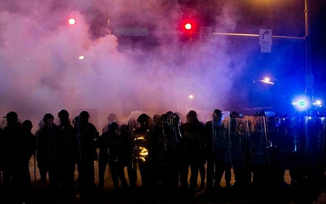 Police advance through a cloud of tear gas as they enforce curfew, Tuesday, April 28, 2015, in Baltimore, a day after unrest that occurred following Freddie Gray's funeral. (AP Photo/Matt Rourke)