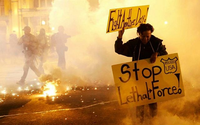 A woman runs for safety as police throw tear gas canisters while enforcing curfew, Tuesday, April 28, 2015, in Baltimore, a day after unrest that occurred following Freddie Gray's funeral. (AP Photo/Patrick Semansky)