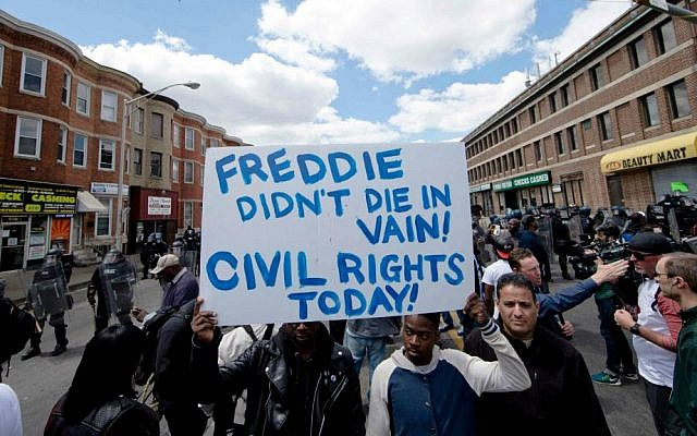 People gather Tuesday, April 28, 2015, in Baltimore, in the aftermath of rioting following Monday's funeral for Freddie Gray, who died in police custody. (AP Photo/Matt Rourke)