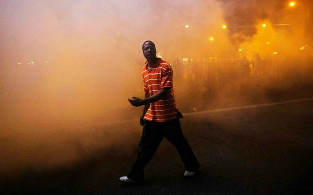 A protester walks through a cloud of tear gas as police in riot gear advance on the crowd after a 10 p.m. curfew went into effect in the wake of Monday's riots following the funeral for Freddie Gray, Tuesday, April 28, 2015, in Baltimore. (AP Photo/David Goldman)