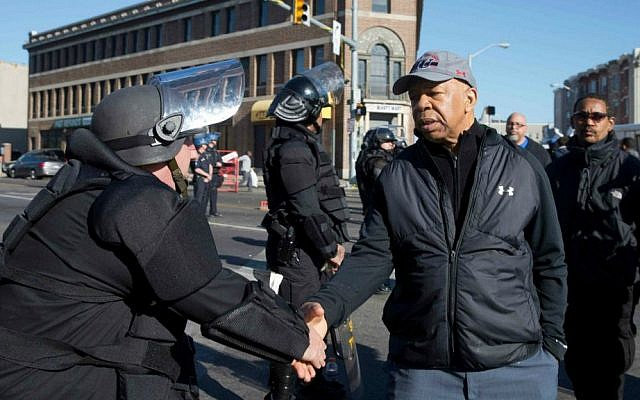 US Rep. Elijah Cummings (D-Maryland), shakes hands with a Maryland State Trooper Tuesday, April 28, 2015, in the aftermath of rioting following Monday's funeral for Freddie Gray, who died in police custody. (AP Photo/Matt Rourke)