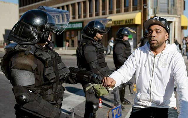 A man on a bicycle greets Maryland State Troopers Tuesday, April 28, 2015, in the aftermath of rioting following Monday's funeral for Freddie Gray, who died in police custody. (AP Photo/Matt Rourke)